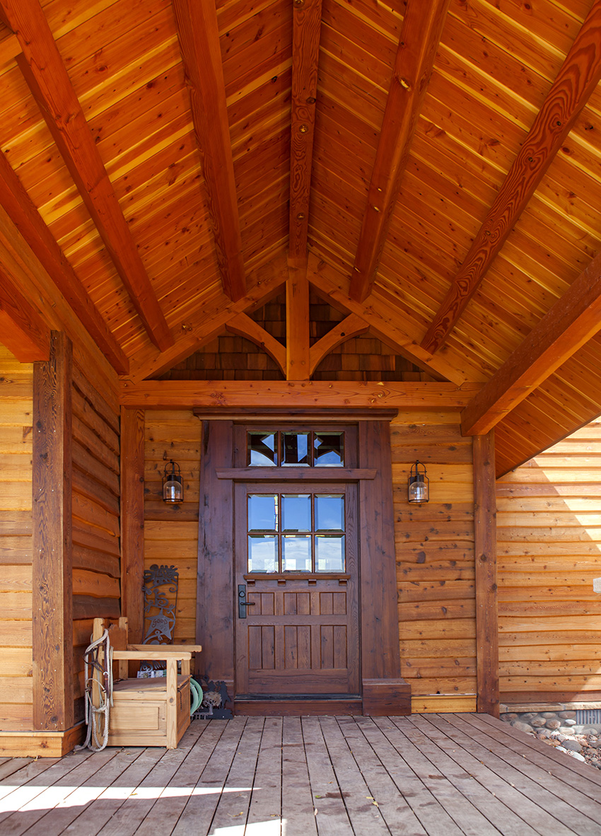 Timber frame front porch with dark stained entry door