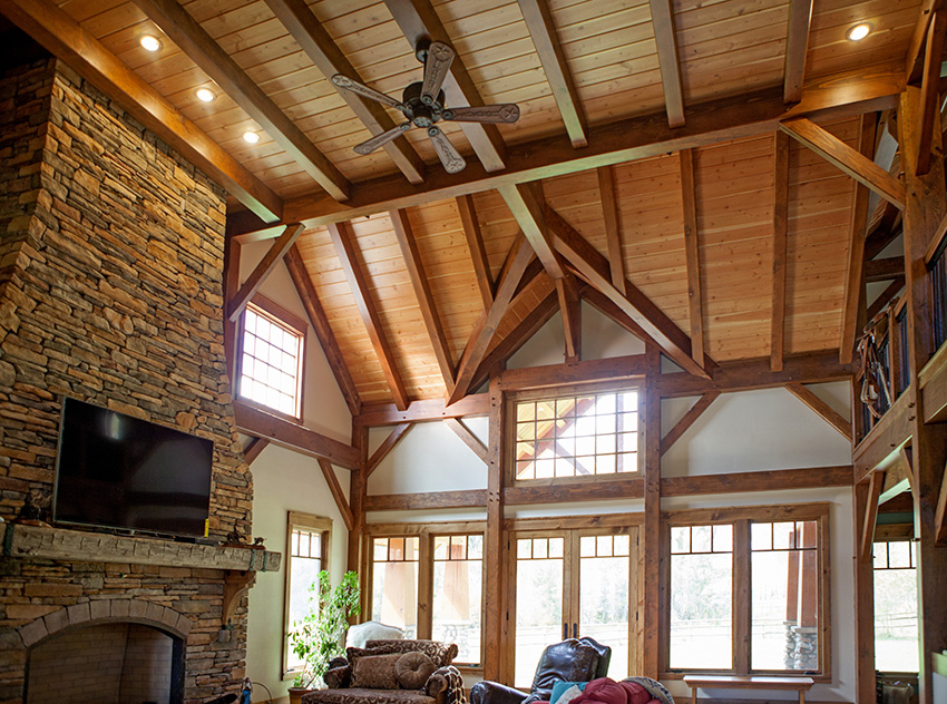 Great room with timber frame beams along loft ceiling