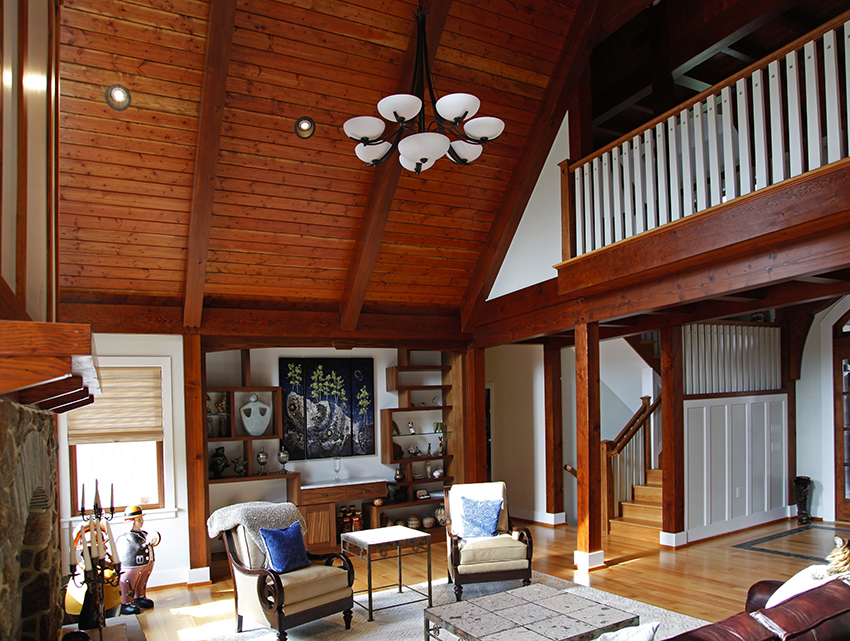 Open concept great room with timber frame balcony