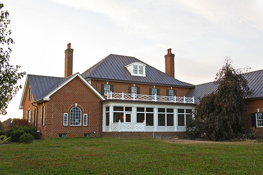 Back porch with white timber frame details behind brick home