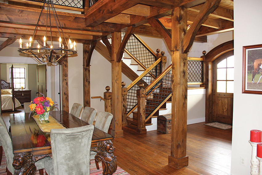 Open concept dining and living area with heavy wood beams