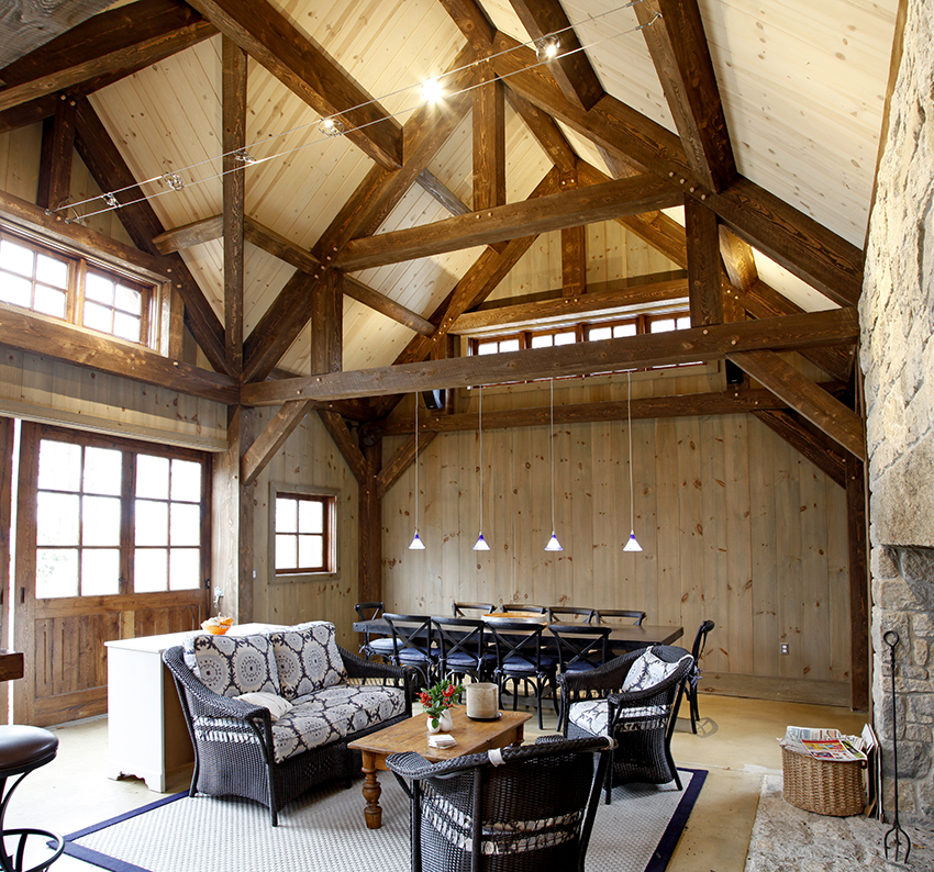 Pool house living area with exposed beams and wicker furniture