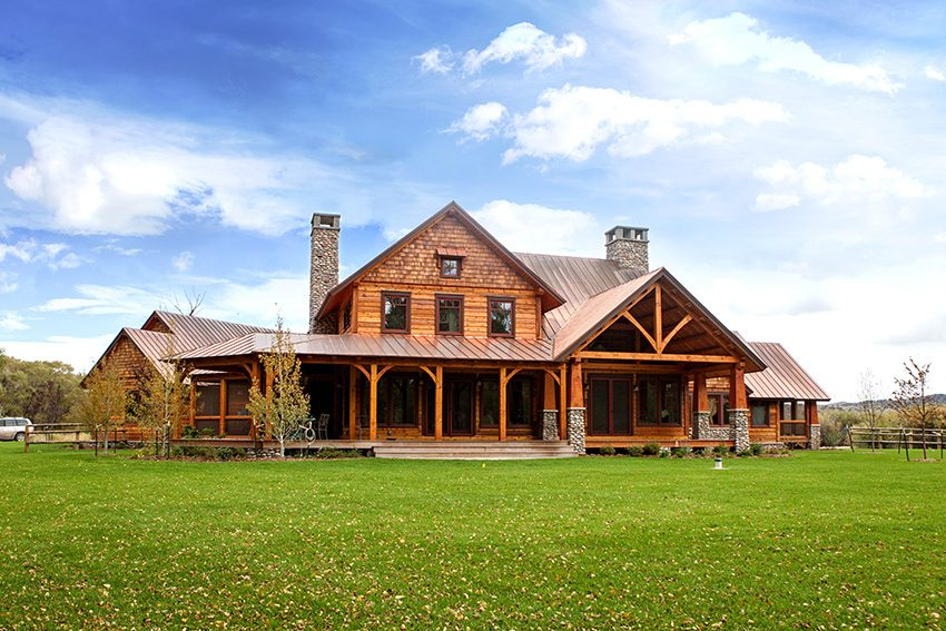 Timber frame home with expansive porch and stone columns