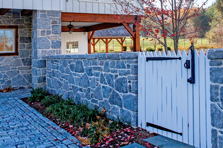 A stone wall with a custom wooden picket gate