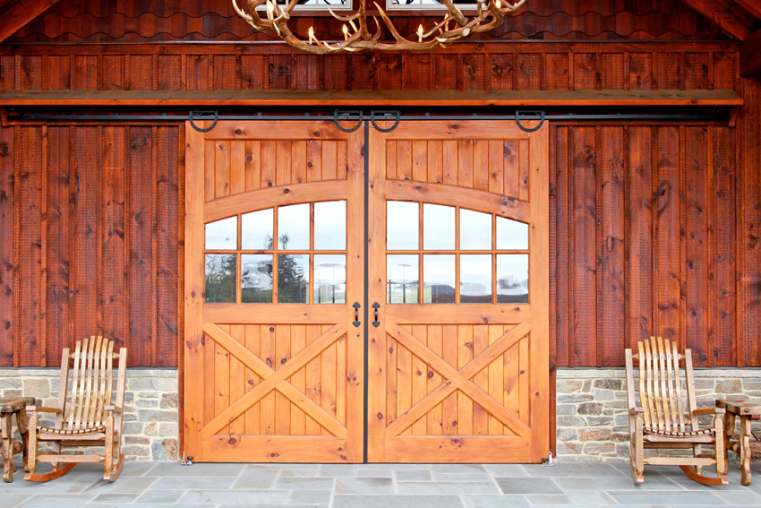 Barn entrance showing a solid door sliding barn doors with window