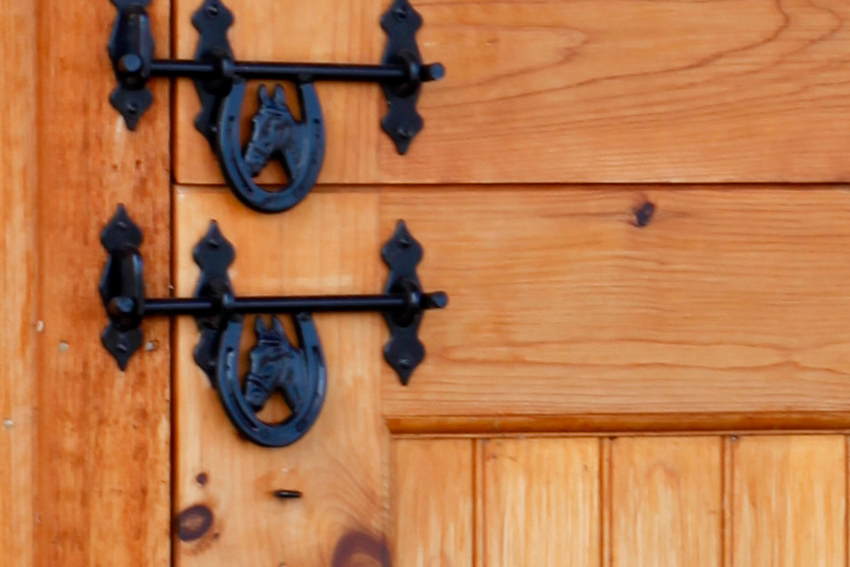 Customized stable slide latch with horse head handles on a stable door