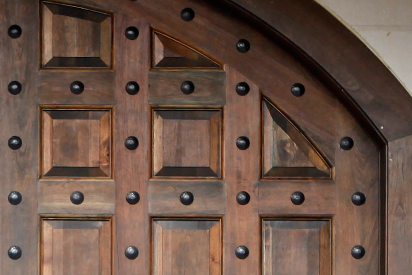 Exterior view of a wooden arched door with studs