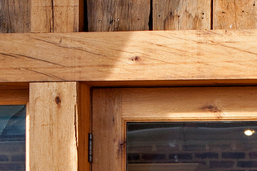 Detail of a door frame made from clear finished reclaimed wood