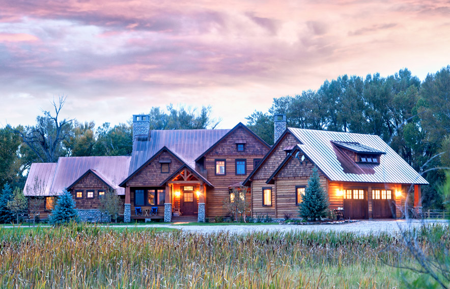 A timber frame home illuminated at dusk under a brilliant sunset